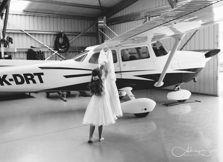 Image of flower girl with an airplane at Martinborough airstrip taken by Alicia Scott - Wairarapa wedding photographer